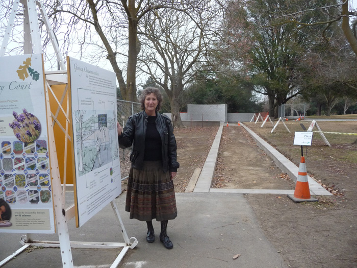 Dr. Diane Ullman shows off some new signage in the gardens, describing an innovative project combining science and art.