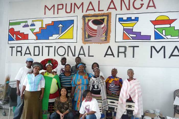 Market staff and participating crafters gather under the official banner of the event, decorated with the logo and with Ndebele mural paintings. Photo by Betty J. Belanus