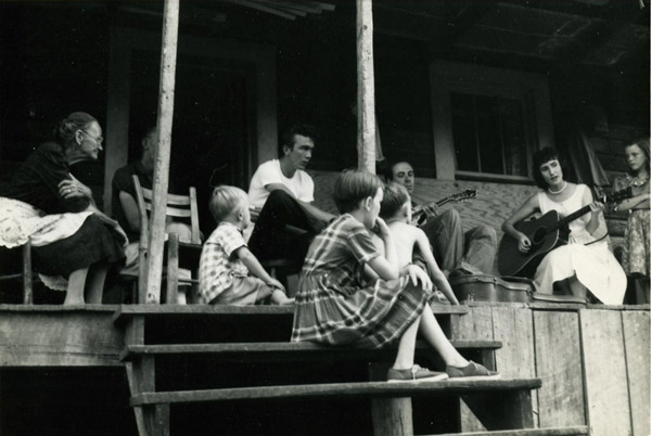 This photograph, from the Ralph Rinzler Papers, was taken around 1960 while on a trip to record Clarence Ashley and Doc Watson. Hazel is seen here on the porch of Sophronie Miller Greer, a neighbor of Watson's.