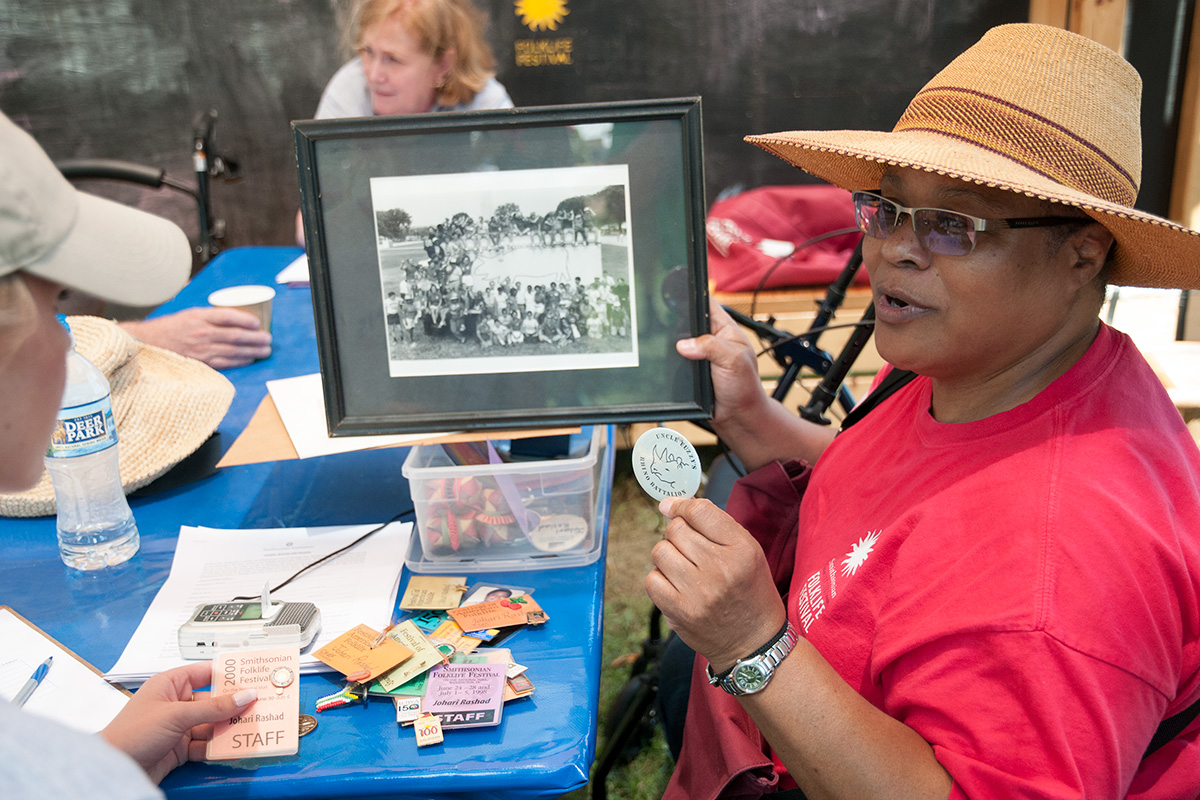 Longtime staff member and volunteer Johari Rashad shows off Festival memorabilia at Reunion Weekend, while Pam Hansen conducts oral history interviews in the background. Photo by Joe Furgal, Ralph Rinzler Folklife Archives