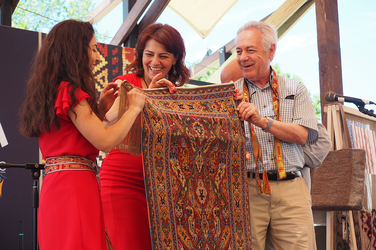 Weavers Diana Hovhannisyan and Ruzanna Torozyan along with presenter Levon Der Bedrossian show off the completed rug on the Hyurasenyak Stage at the 2018 Smithsonian Folklife Festival. Photo by Julie Byrne, Ralph Rinzler Folklife Archives