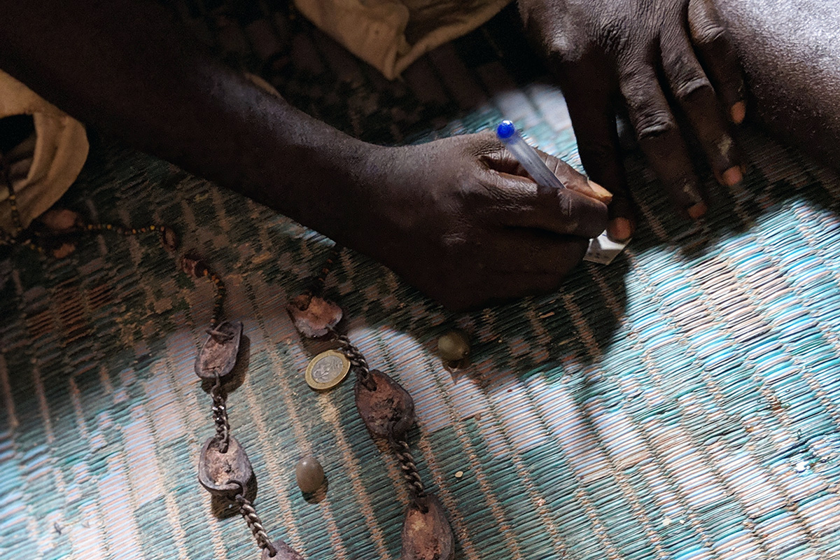 Fa diviner Koffi Akossa uses chains of kola nut pieces and other materials to gain insight into clients' situations. Photo by Rebecca Fenton