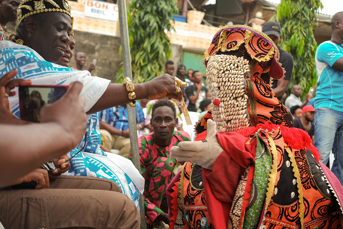 Dancemaker Koffi Alade interacts with an Egungun, a cloth masquerade embodying an ancestor, at a community performance near Cotonou, Benin. Photo by Rebecca Fenton