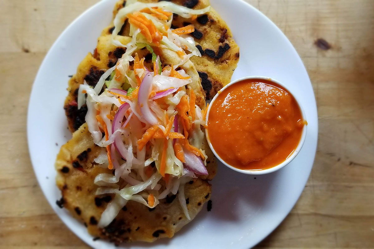 Pupusas with curtido on top and salsa rojo on the side. Photo by Kathy Phung