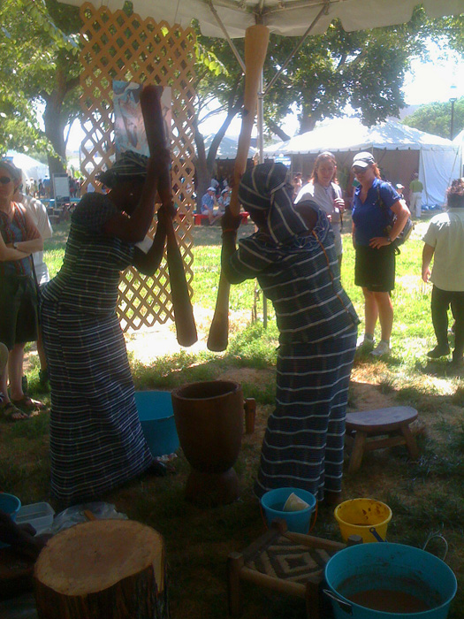 Braimah Shietu and Rukayu Amidu work in unison to demonstrate the shea butter production process in the Peace Corps program of the Festiva