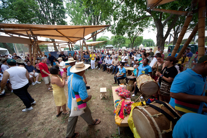 Visitors and artists interact under the guadua (bamboo) tents in the Colombia program area