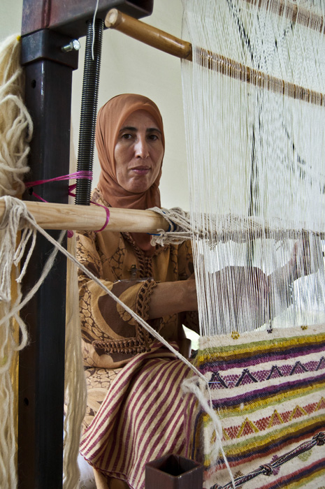 Moroccan weaver Fatima Akachmar works at her loom.
