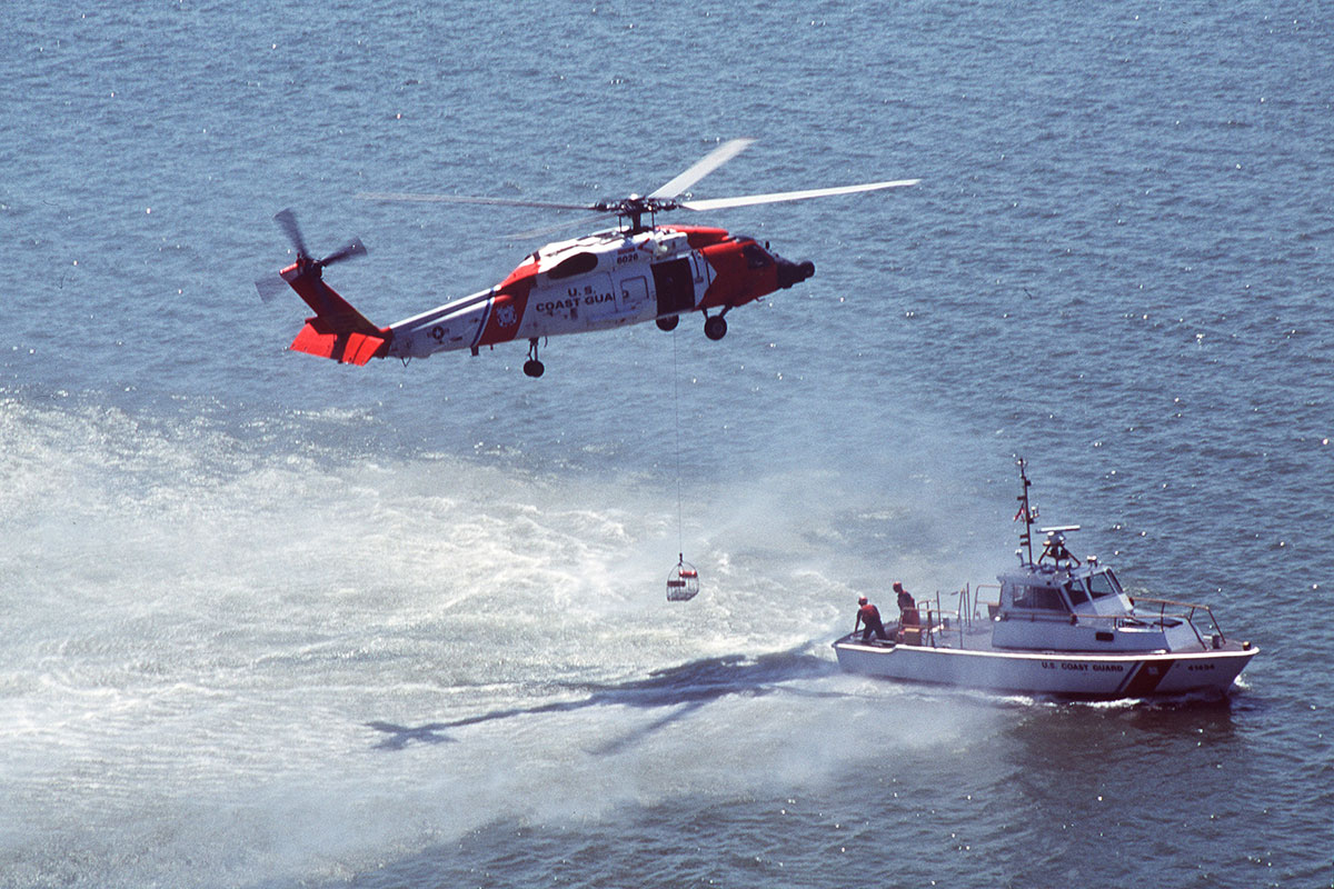 Coast guardsmen aboard the Jayhawk helicopter and a 41-foot utility boat pictured at left are demonstrating their skills during Coast Guard Missions Day in Yorktown, Virginia. USCG photo by PA2 Jacquelyn Zettles, courtesy the U.S. Coast Guard