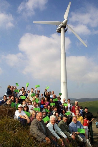 Locals celebrate the opening of the first community-owned wind turbine which was installed in 2003 above the Centre for Alternative Technology near Machynlleth, Wales. The turbine is owned and managed by the surrounding community, and the power it generates eliminates over 77 tons of carbon emissions each year. Photograph courtesy of the Center for Alternative Technology.