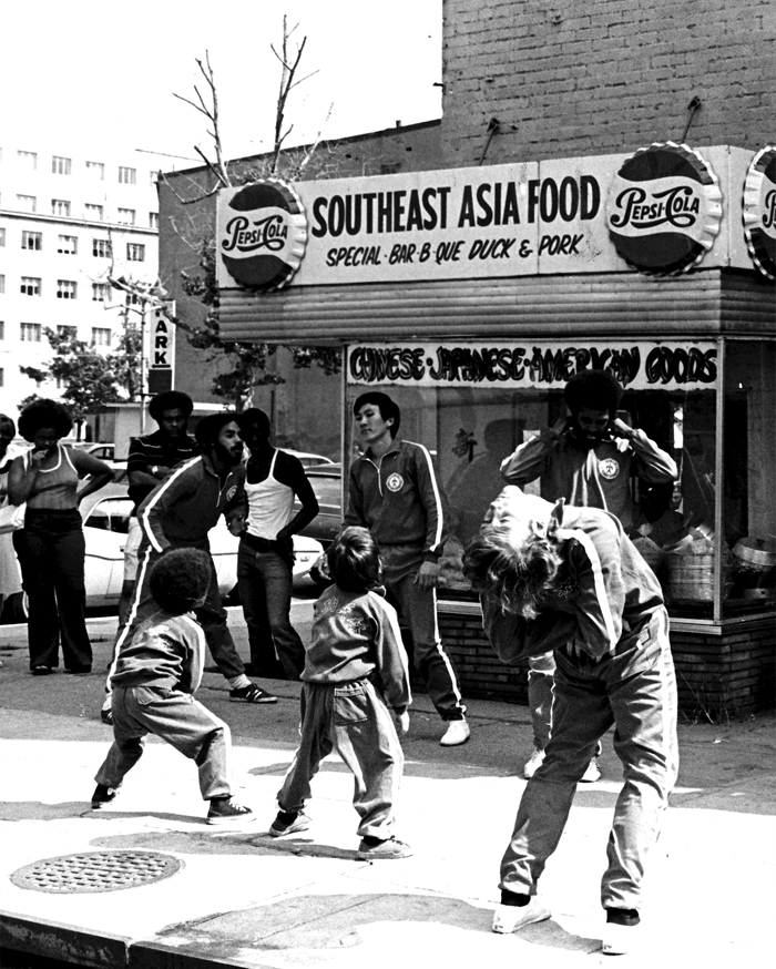 Members of Willy Lin's Kung-fu School loosen up before class at the corner of Sixth and H Streets in Northwest Washington, ca. 1971. At this time, the local Asian Pacific American community was represented by restaurants that spanned more than one nation of origin, with African Americans and APAs participating in joint activities.