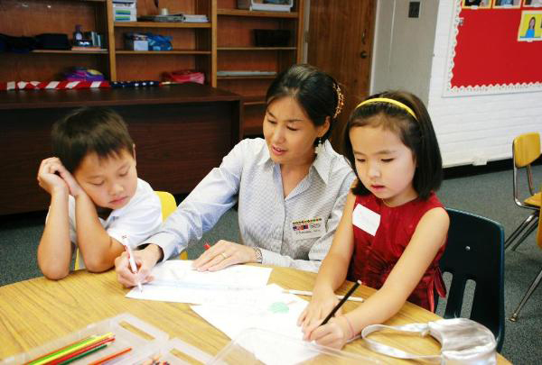 Kindergarten teacher Khandmaa Wyckoff works with two students at a Virginia-based Mongolian school.