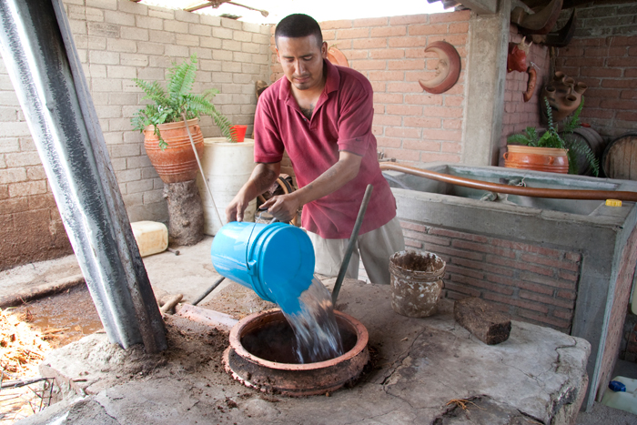 Water and fermented maguey are poured into a brick still or alambique for mezcal distillation.