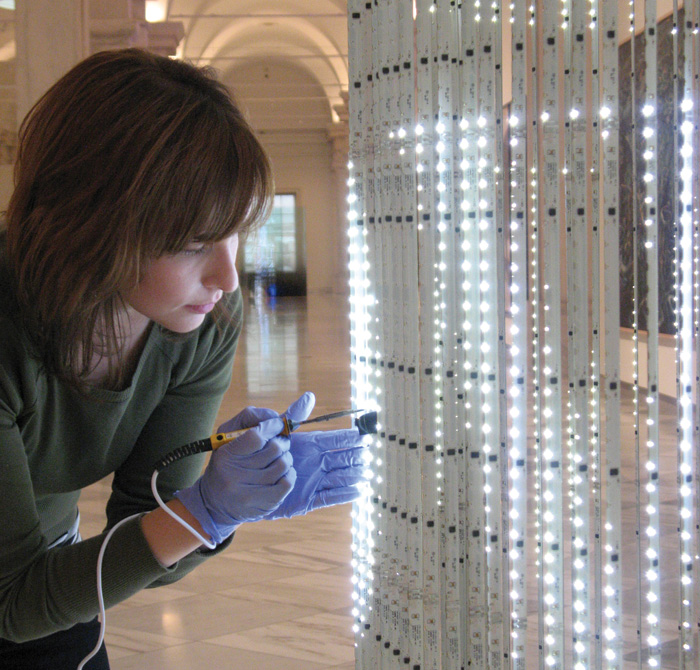 Conservation technician Susan Edwards maintains Jenny Holzer's light sculpture at the Smithsonian American Art Museum.