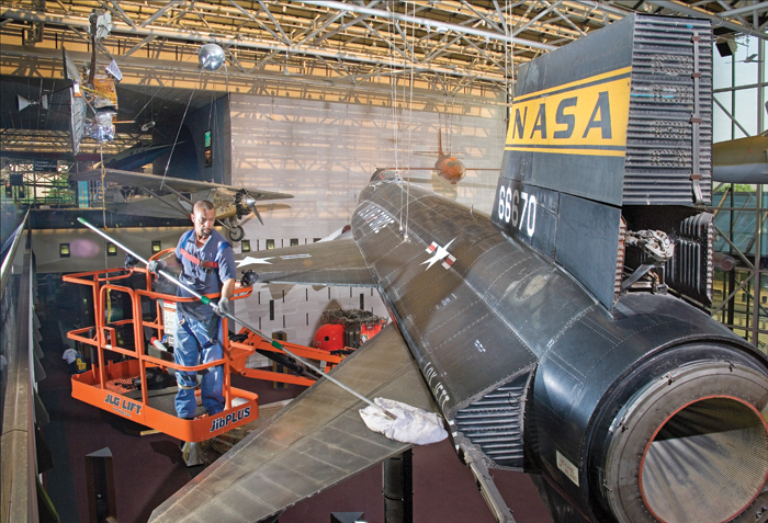 Harrison Jones, a member of the objects cleaning crew at the National Air and Space Museum, dusts the X-15 aircraft hanging in the Milestones of Flight Gallery.