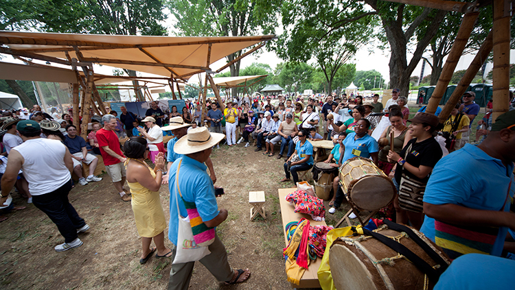 Visitors and artists interact under the guadua (bamboo) tents in the Colombia program area.
