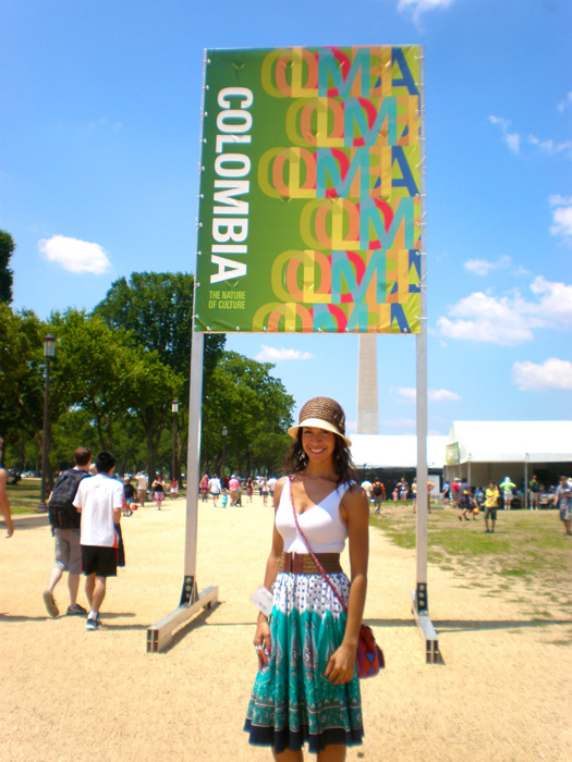 Kiley Guyton Acosta in front of the 2011 Smithsonian Folklife Festival Colombia program sign and the Washington Monument.
