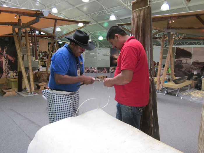 "Hermes Romero from the Southeastern Plains makes a key chain for Jhon Jairo ""Guama"" Amortegui, a yipero (jeep driver) from the Coffee region."