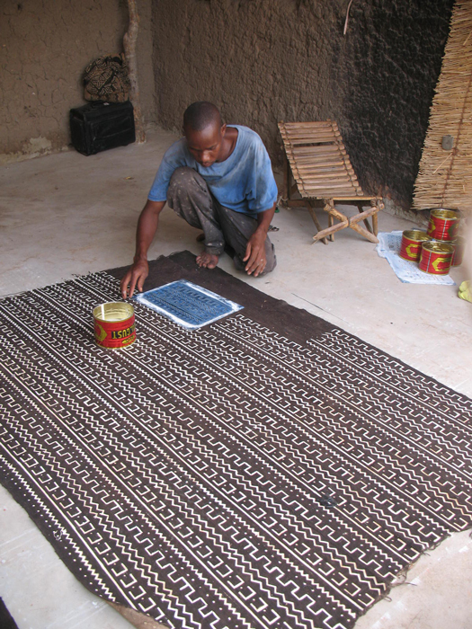 Moussa Fofana applies dye to the cloth.