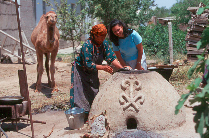 Peace Corps volunteer Vivian Colon bakes bread in a clay oven with her host mother in Turkmenistan.