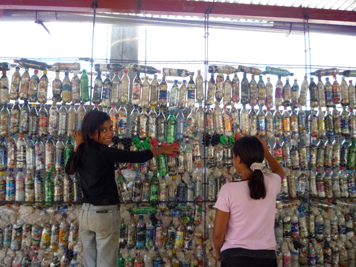 Two Guatemalan students stuff plastic bags into the spaces between plastic bottles.