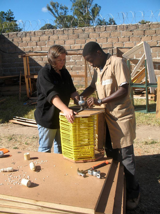 Peace Corps volunteer Kristina Denison and Bernard Kiwia assemble a pedal-powered washing machine.