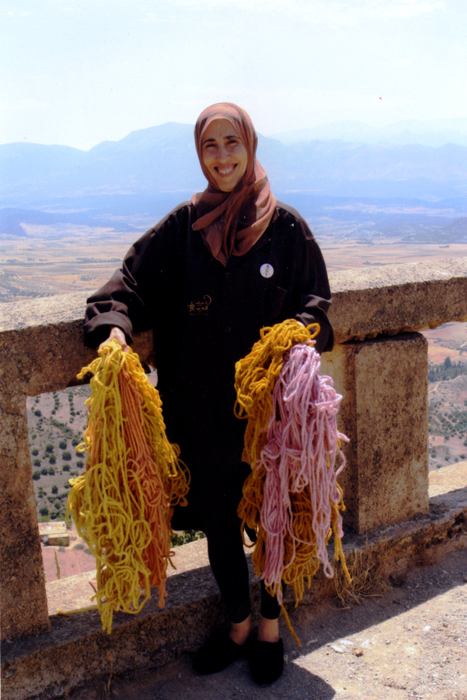 With the Middle Atlas mountain range in the background, Fatima Akachmar holds batches of natural-dyed wool yarn.