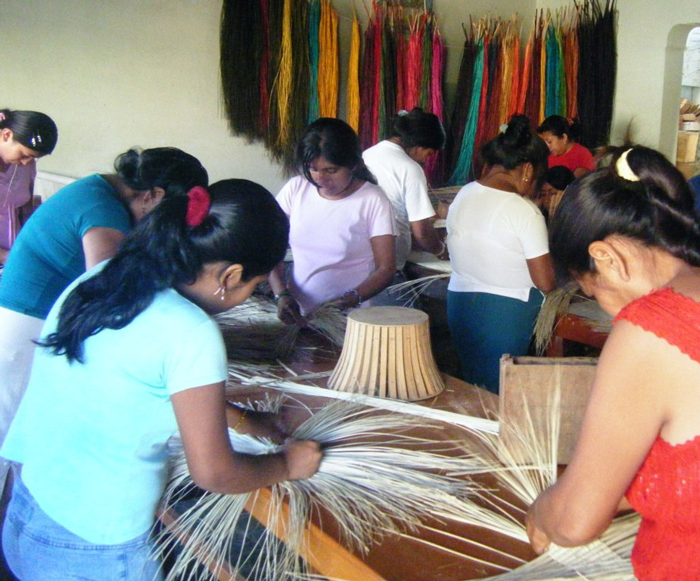 Women from the Virgen del Perpetuo Socorro, an artisan association in northern Peru, weave straw into baskets and hats.