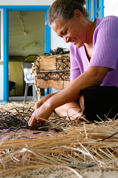 Mele Vaikeli cuts strips of prepared pandanus leaves to a uniform width.