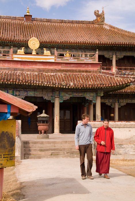 Peace Corps volunteer Sean Speer walks with a monk in a Mongolian monastery. Sean used his business skills to help the monks create a book about their monastery for tourists.