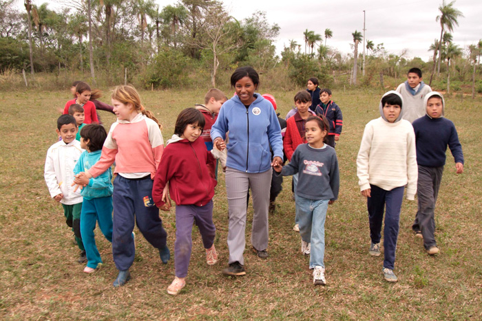 Peace Corps volunteer Tara Taylor walks with her students in Paraguay.