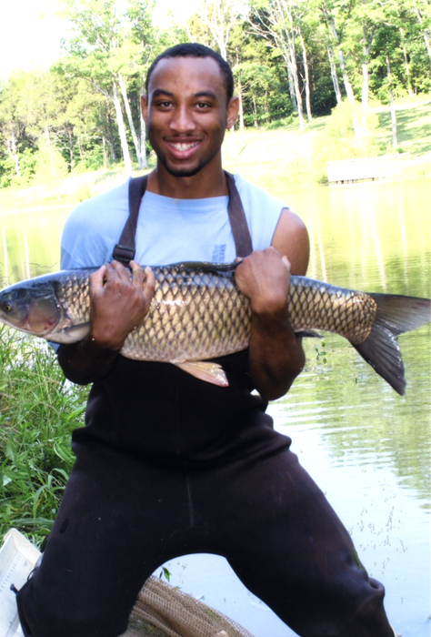 Undergraduate student Steven Patton holds a common carp during a pond population assessment at Kentucky State University's Environmental Education Center