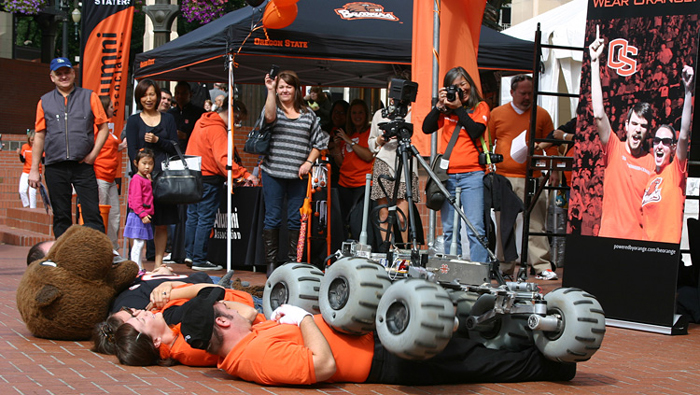 Oregon State University students guide a robot over the university mascot and other volunteers.district.
