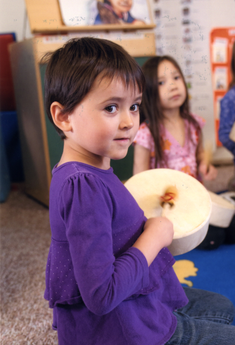 A child participates in a drumming activity in this Head Start classroom.