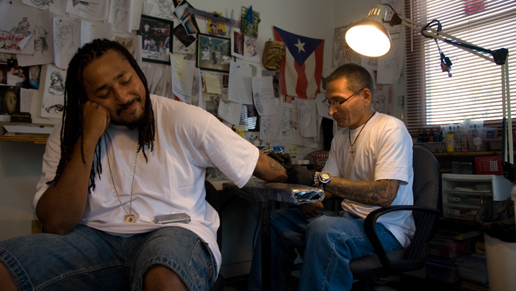 "Charles ""Coco"" Bayron creates a tattoo on the arm of Q Monts at Nu Flava Ink tattoo parlor on Martin Luther King Avenue SE. Photograph by Susana Raab / Anacostia Community Museum"