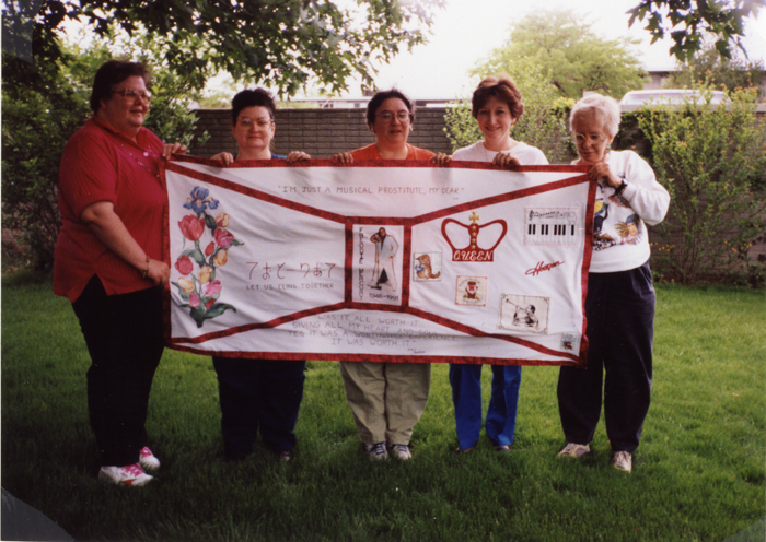 Sarah Leigold, Carol Hunterton, Sharon Fetter, Linda Neel, and Darien Duck hold the panel they made for Freddie Mercury, block 02442.