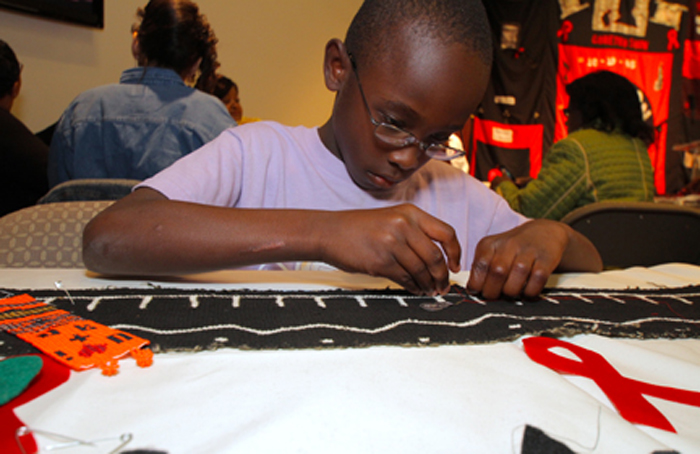 A boy takes part in a Call My Name workshop in Houston, Texas, by sewing fabric cut-outs onto a panel.