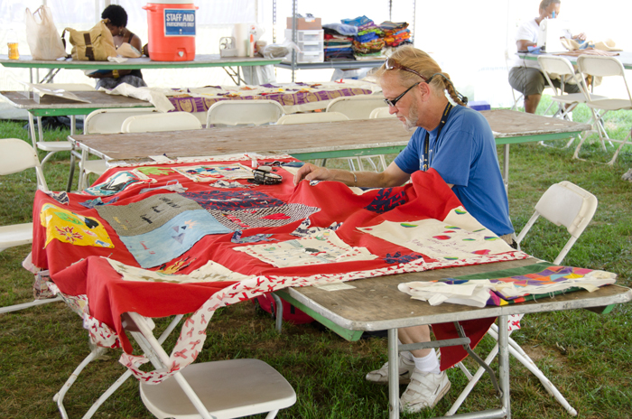 "Participant Father Joseph ""Rick"" McCormack repairs a panel of The AIDS Memorial Quilt at the 2012 Smithsonian Folklife Festival."