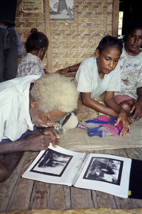 Ikoi Uaini looks at historic photos taken by F.E. Williams in 1922 with his granddaughter Rose and daughter-in-law Kathleen in the village of Mapaio, Purari Delta, Papua New Guinea.