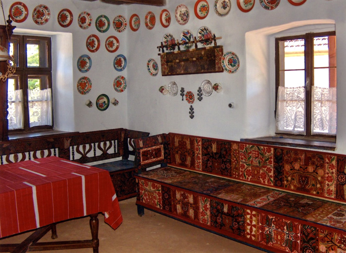 This traditional Kalotaszeg room features painted furniture, homespun textiles, and hand-painted ceramic plates used as wall decoration.