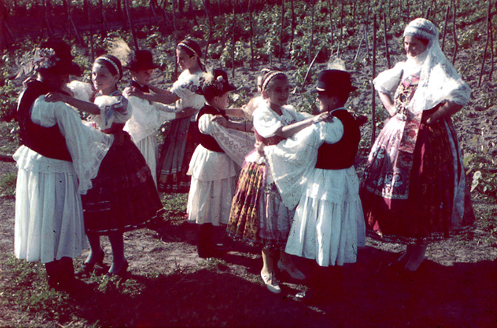 Children in traditional costumes dance in Sárköz, ca. 1930.