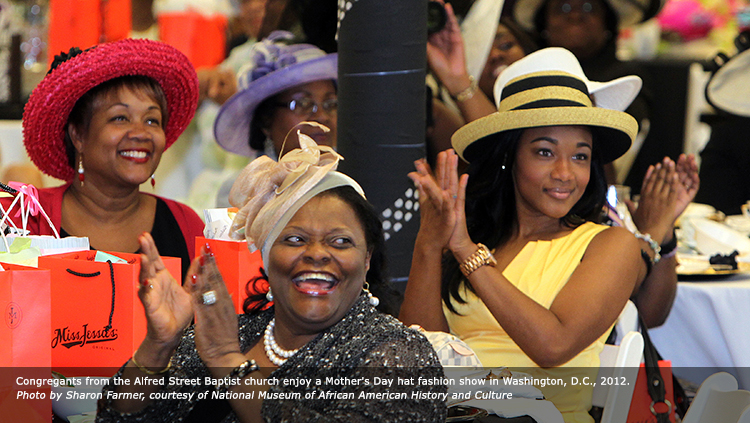 Congregants from the Alfred Street Baptist church enjoy a Mother's Day hat fashion show in Washington, D.C., 2012. Photo by Sharon Farmer, courtesy of National Museum of African American History and Culture