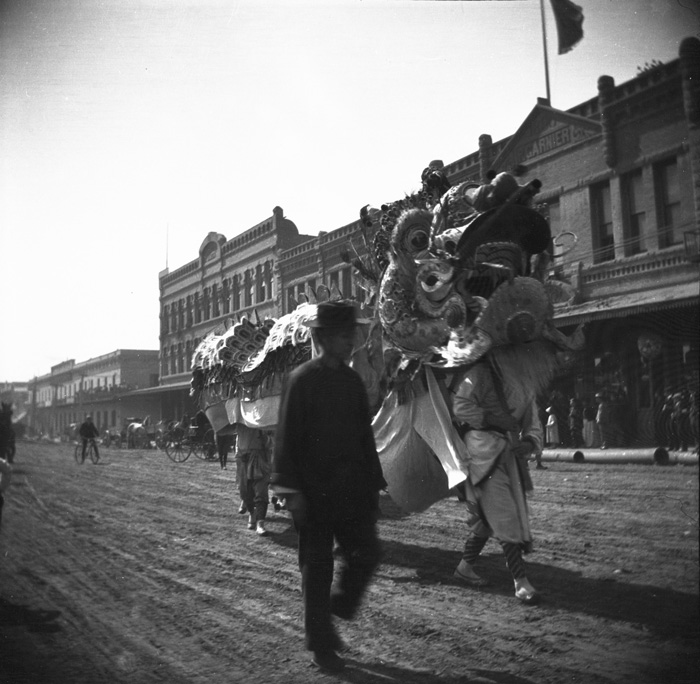 A dragon dance group takes a break as they process down North Los Angeles Street during the local Chinese community' New Year's celebration, Los Angeles, ca. 1902.