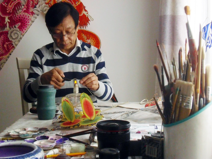 Ha Yiqi works on shaping the frame of a miniature kite, Beijing, 2014.