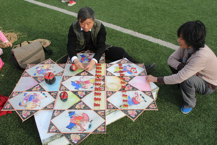 Zhang Wenzhi prepare one of his banyao whistle kites for flight, Nanton, Jiangsu Province, 2014.