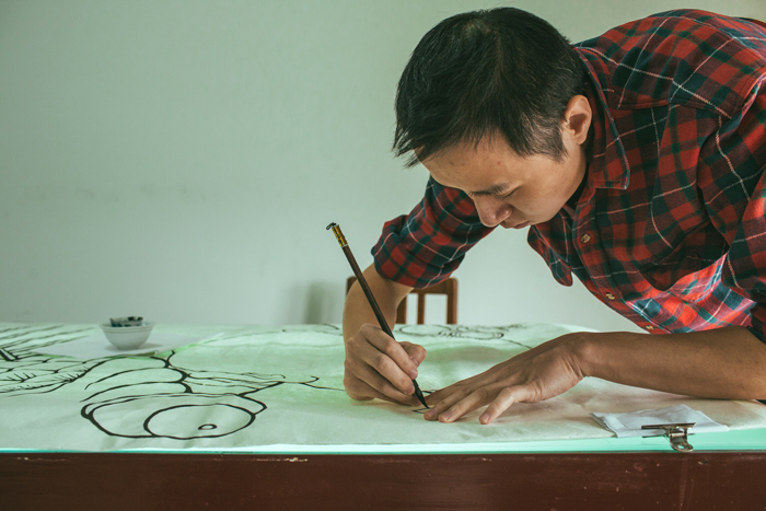 Smithsonian Folklife Festival participant Gao Yan outlines a picture on rice paper.