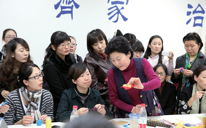 Jin Yuanshan leads a hands-on patchwork activity during an exhibition of her work.
