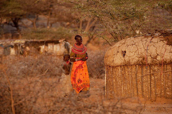 A Samburu woman walks with a boy in the village of Ngutuk Ongiron, Westgate Conservancy.