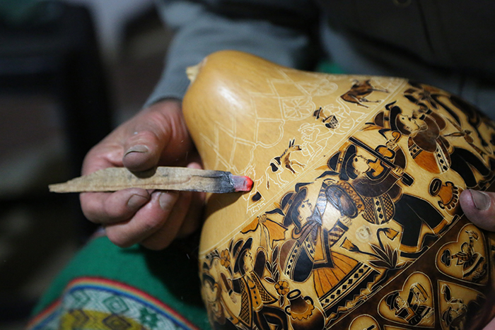 Eleuterio Medina, a mate burilado artist, demonstrates the burning techniques he uses to bring his intricate engravings to life in Cochas Grande, Huancayo.