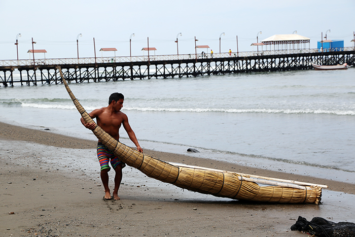 Mateo Valderrama Piminchumo pulls his <em>caballito de totora</em> onto shore. He is one of many who now also use the rafts for surfing.