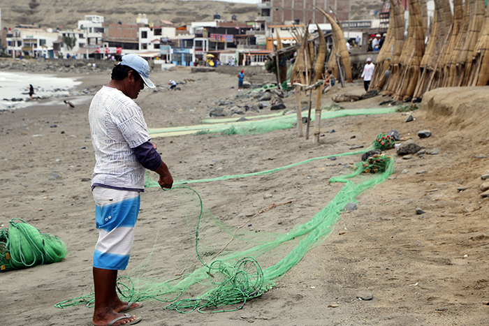 A Huanchaco fisherman prepares his handmade cast net.